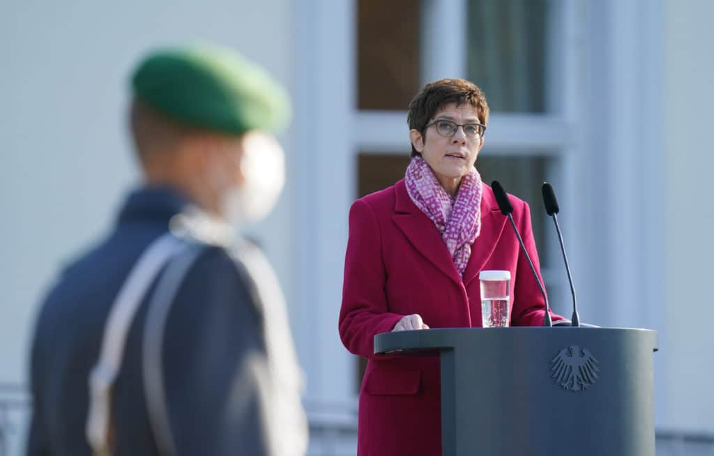 Annegret Kramp-Karrenbauer stands at a podium in a coat. A blurred serviceman is seen in the foreground.