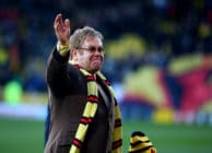 Elton John wearing a Watford FC scarf on a football pitch