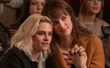 Kristen Stewart and Mackenzie Davis holding hands in Happiest Season