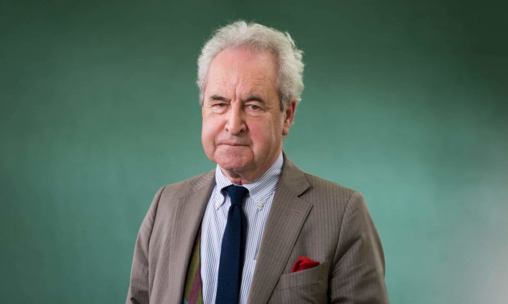 John Banville wearing a suit and tie against a green backdrop