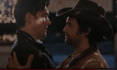 Two men embracing, one wearing a cowboy hat, in the Dashing in December trailer
