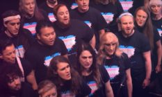 Choir members wearing t-shirts with a heart on in the colours of the trans flag