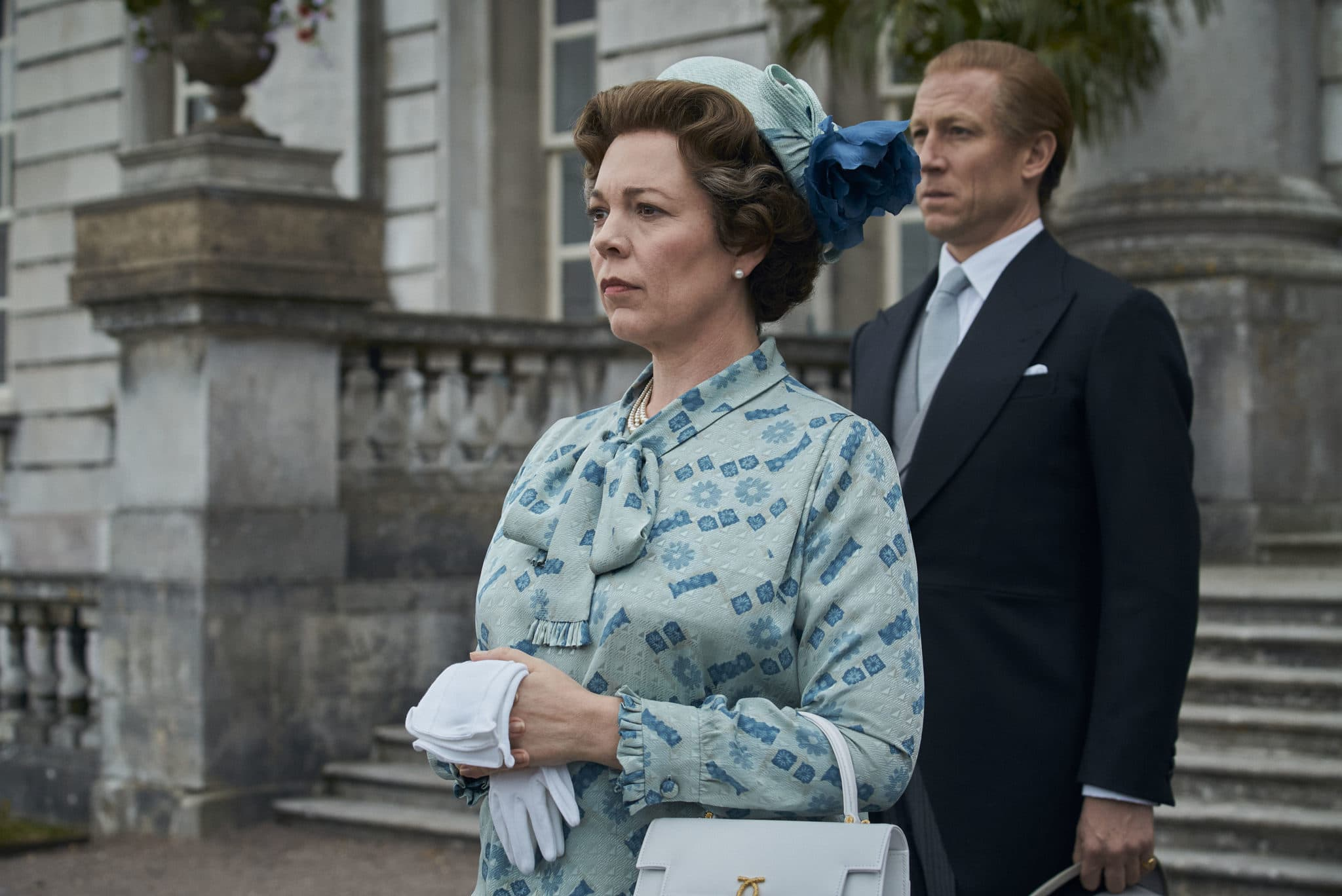 Olivia Colman as the Queen standing on the steps of the palace with Prince Philip behind her, in a duck-egg blue pussy-bow and pillbox hat