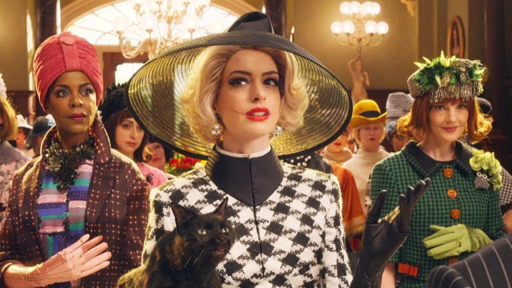 Anne Hathaway in The Witches, wearing a big black hat, blonde hair, and carrying a black cat in a grand ballroom