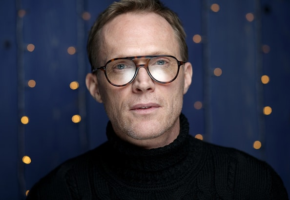 Paul Bettany looking into the camera wearing glasses and a black turtleneck
