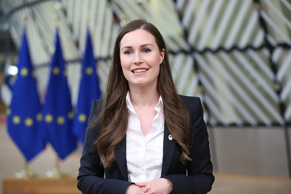 Sanna Marin is smiling in front of EU flags.