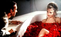 Kevin Spacey leering over a naked young woman in a bath filled with flowers