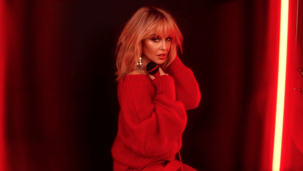 Kylie Minogue looking over her shoulder in a red jumper, a soft red neon lighting her face. She's holding a microphone