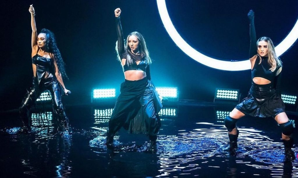 Little Mix dancing in black outfits against a neon light