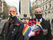 Peter Tatchell and David Bonney holding a rainbow poppy wreath at the Cenotaph