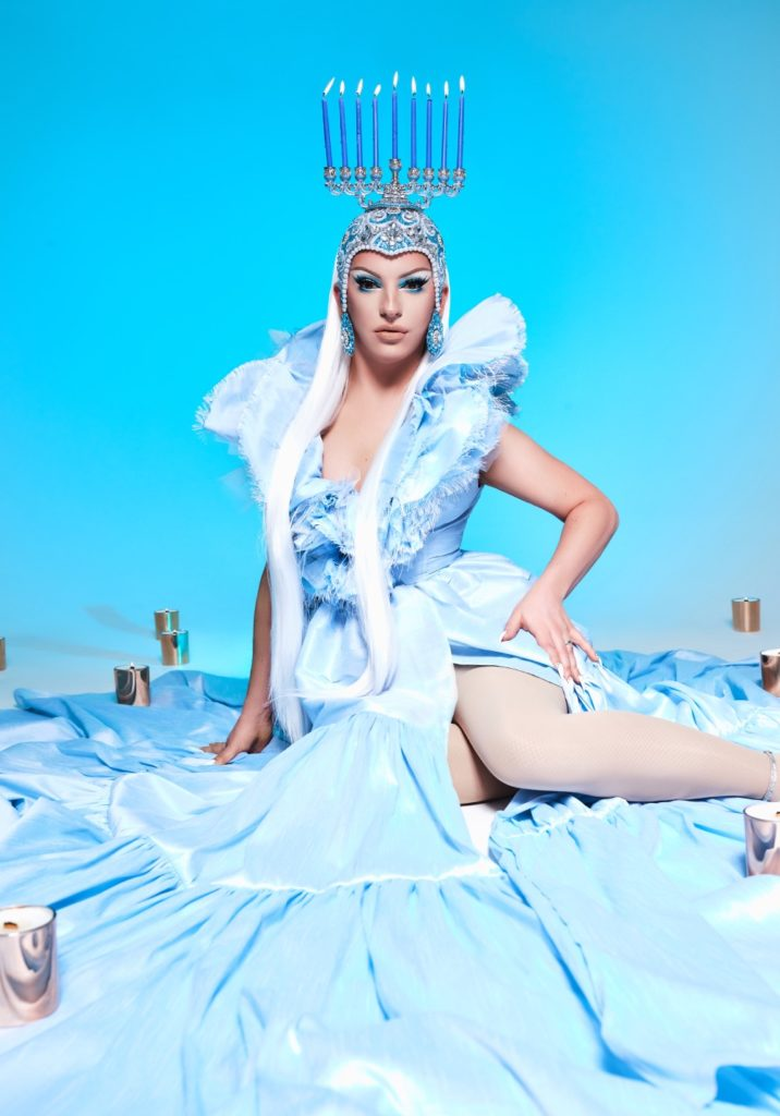 Wide shot of Cracker wearing a menorah headpiece and icy blue gown