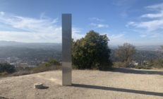 A tall, slim silver monolith at the top of an empty hill
