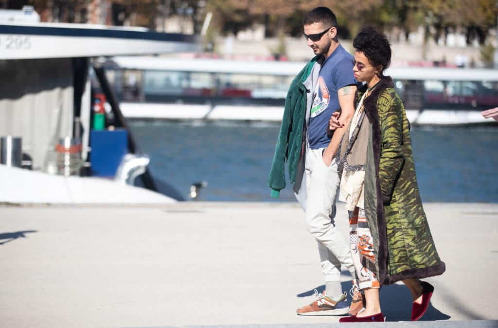 Shia LaBeouf and FKA Twigs walk along a pier with a boat behind them
