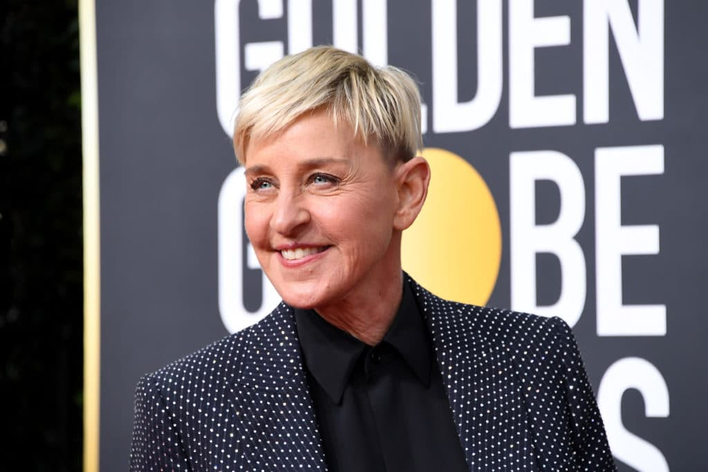 Ellen DeGeneres smile while wearing a grey suit jacket