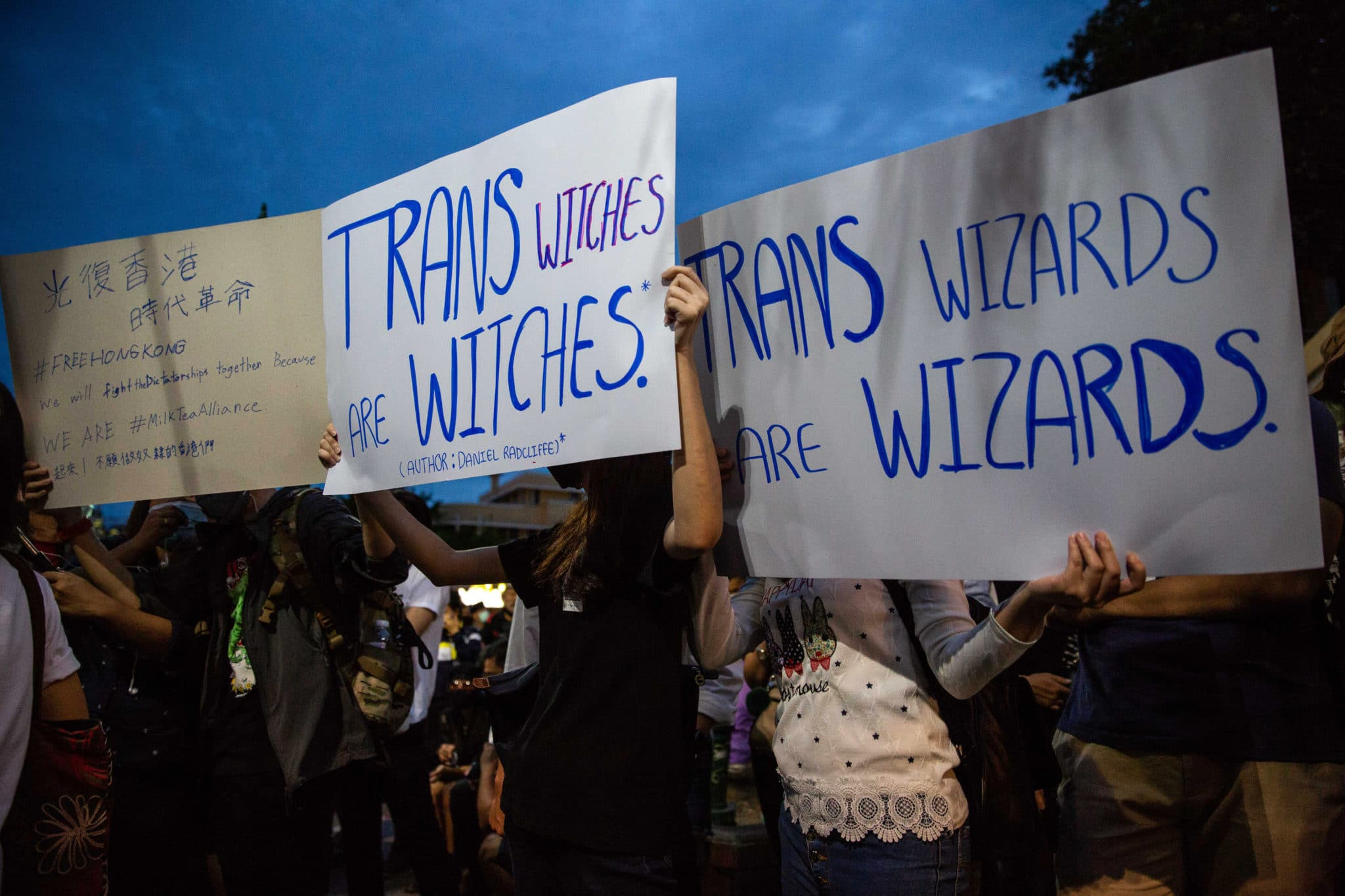 Protesters hold signs calling out JK Rowling as they take part in a Harry Potter themed on August 3, 2020 in Bangkok, Thailand.