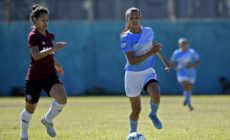 Transgender footballer Mara Gomez of Villa San Carlos vies for the ball with Luciana Nievas of Lanus