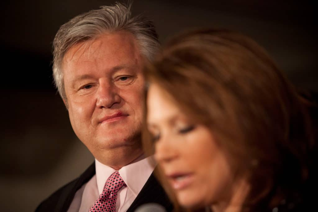 Marcus Bachmann wears a suit and red tie