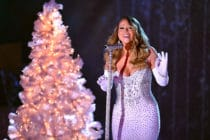 Mariah Carey performs in a white diamanté dress with a white Christmas tree behind her