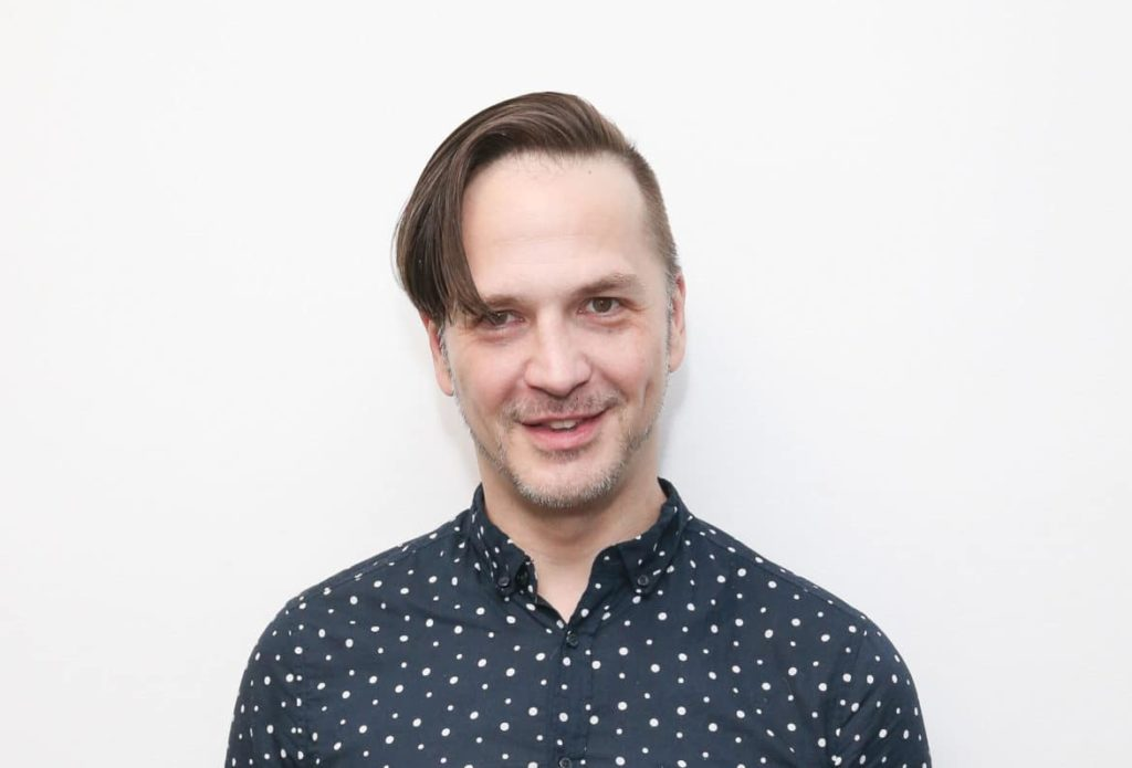 Michael Alig in a printed blue shirt against a white background
