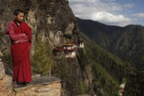 A monk stands on the mountaintops, a monastery in view behind him on the cliffs