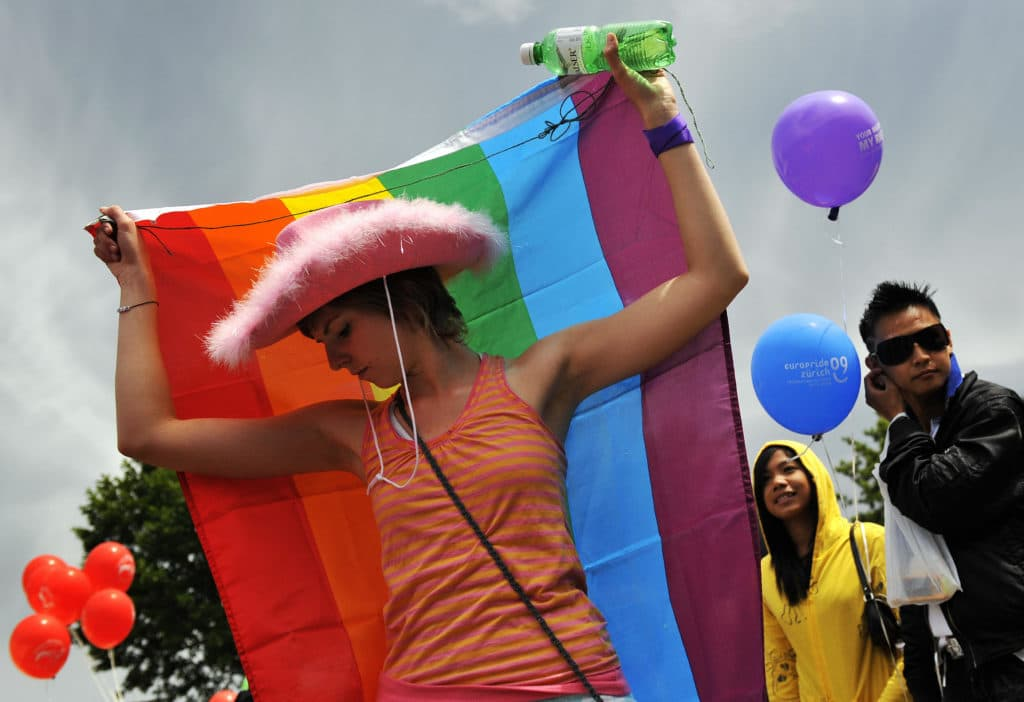A Pride-goer in a pink cowboy hat with a rainbow flag around her back