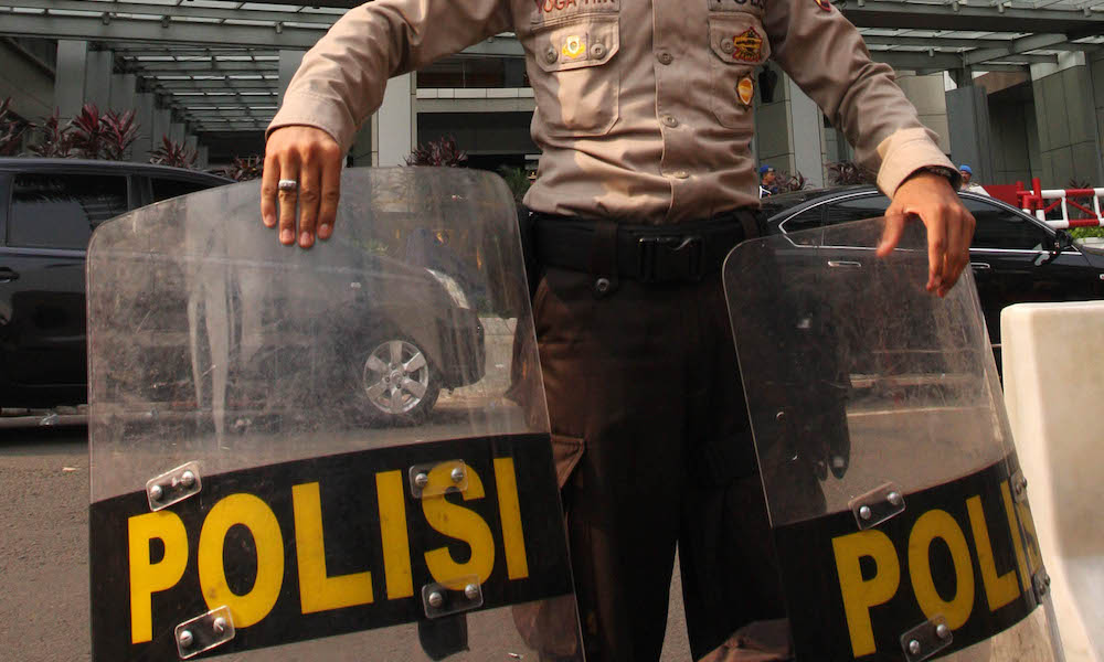 A police officer stands guard at the front of the Marriott hotel in Jakarta, Indonesia