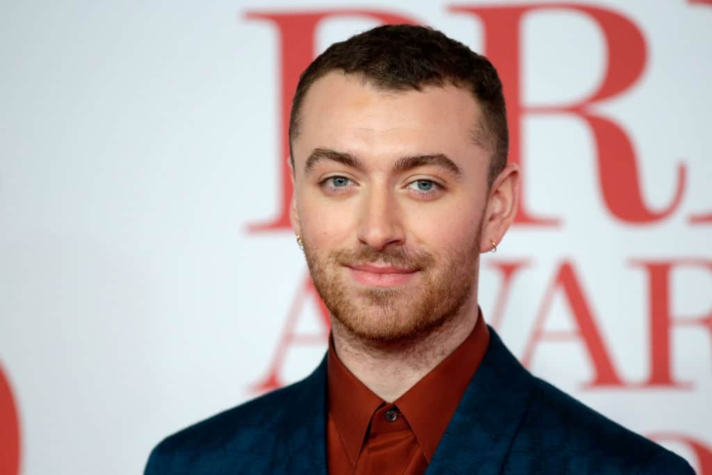 Sam Smith smiles in a buttoned-up burgundy shirt and black blazer