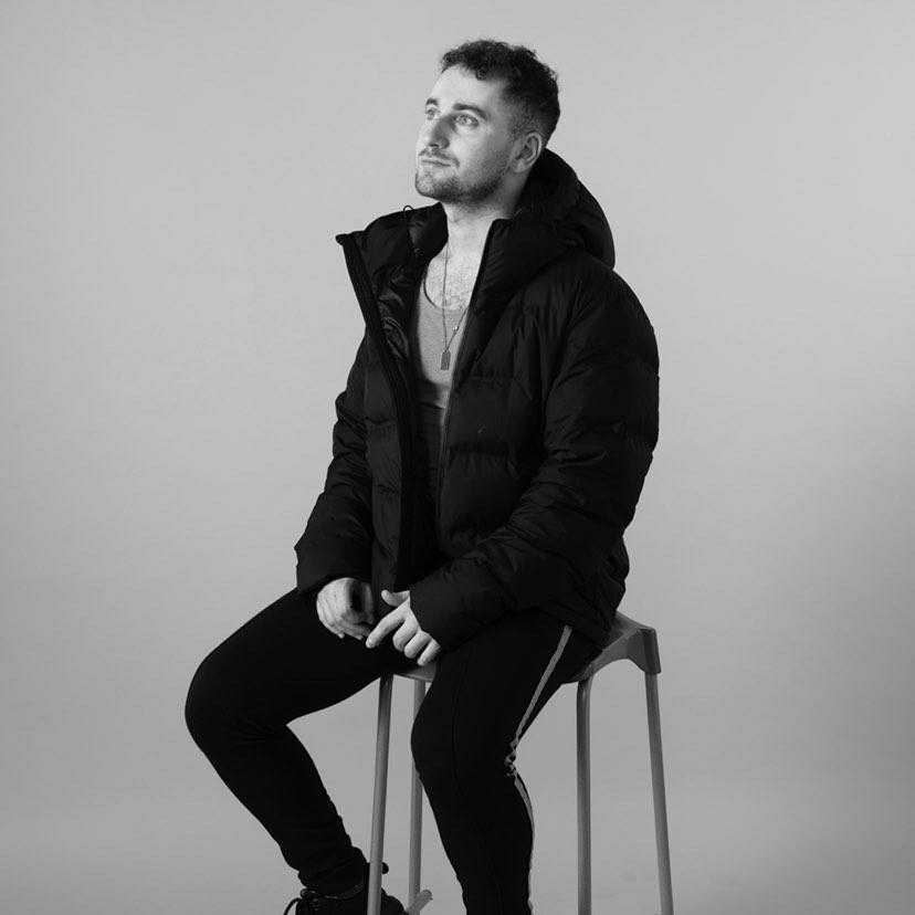 A black and white picture of Ciaron sitting on a stool