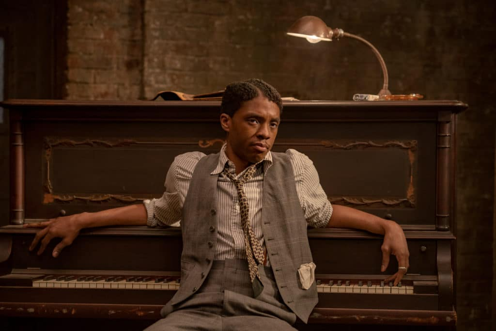 Chadwick Boseman sitting at a piano, facing away from the keys, in a grey waistcoat and low-slung tie