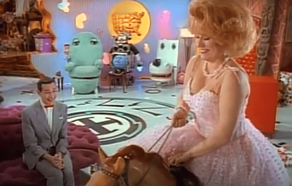 Pee-wee Herman watching Miss Yvonne riding a mechanical horse