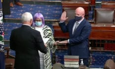 Bisexual senator Kyrsten Sinema (C) holds the Bible as Mark Kelly (R) is sworn in by Mike Pence. (Twitter)
