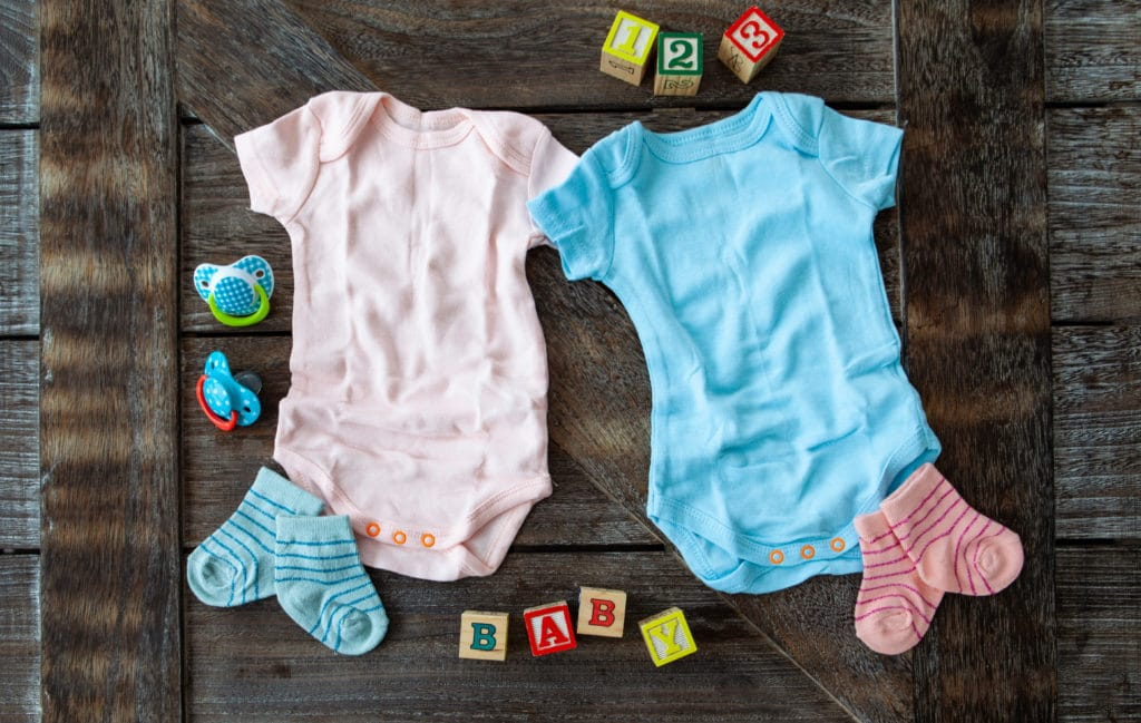 A pink and blue baby onesie with toys surrounding them
