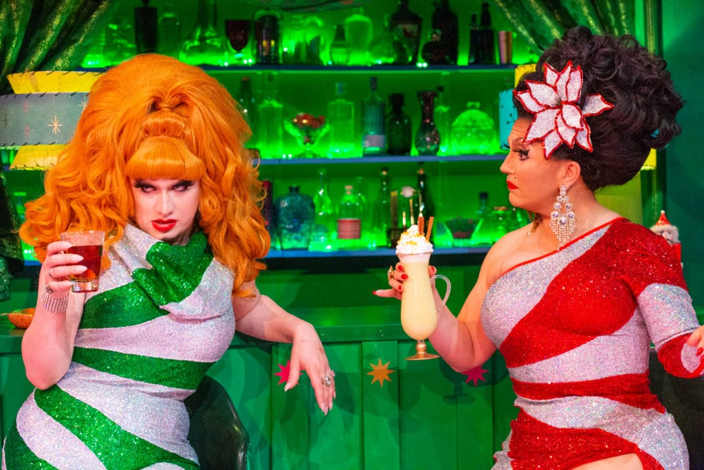 BenDeLaCreme and Jinkx Monsoon in matching candy-striped dresses, holding drinks
