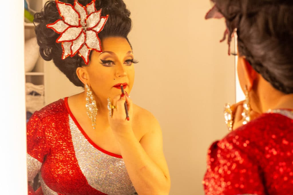 BenDeLaCreme applying lipstick in a mirror