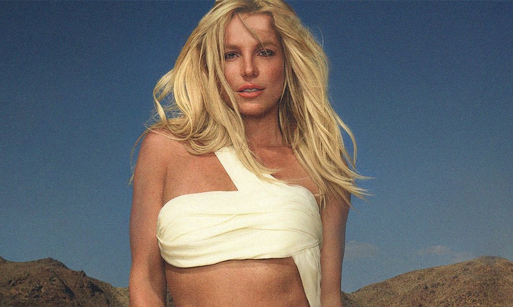 Britney Spears in a white asymmetric crop top standing in a desert