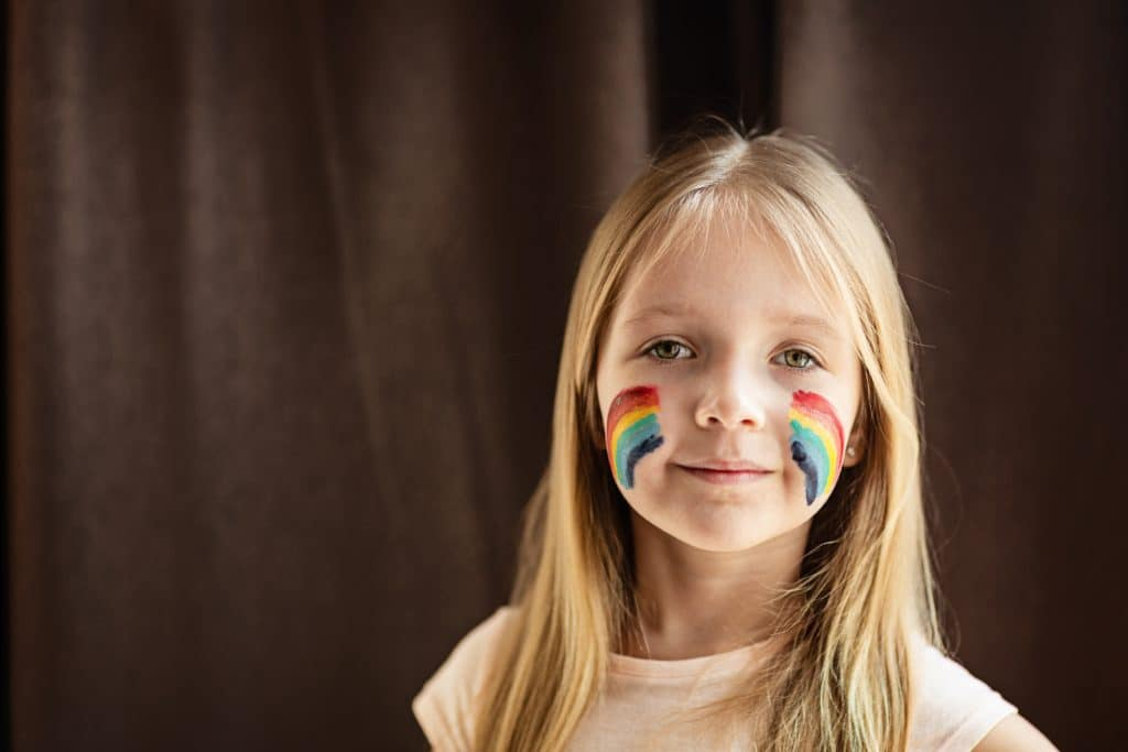 A child with rainbow LGBT+ Pride flag face paint on each of her cheeks