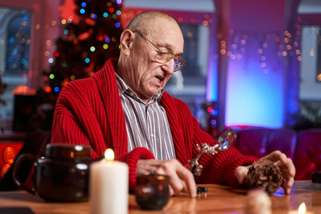 Portrait of a concentrated and serious santa claus working at table and preparing decoration from cone in colourful and decorated cosy room.