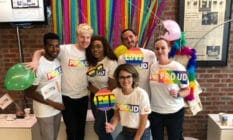 Members of Pride FT, the LGBT+ wing of the Financial Times, pose with rainbow 'proud' t-shirts and rainbow FT signs