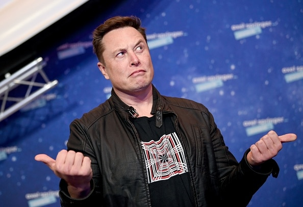 Elon Musk gestures while wearing a graphic print t-shirt and a black jacket