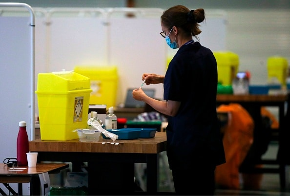 A nurse carries a syringe full of the coronavirus vaccine in a make-shift NHS vaccine centre