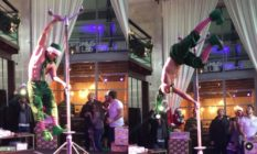 Topless man dressed in elf trousers and a hat pole dancing