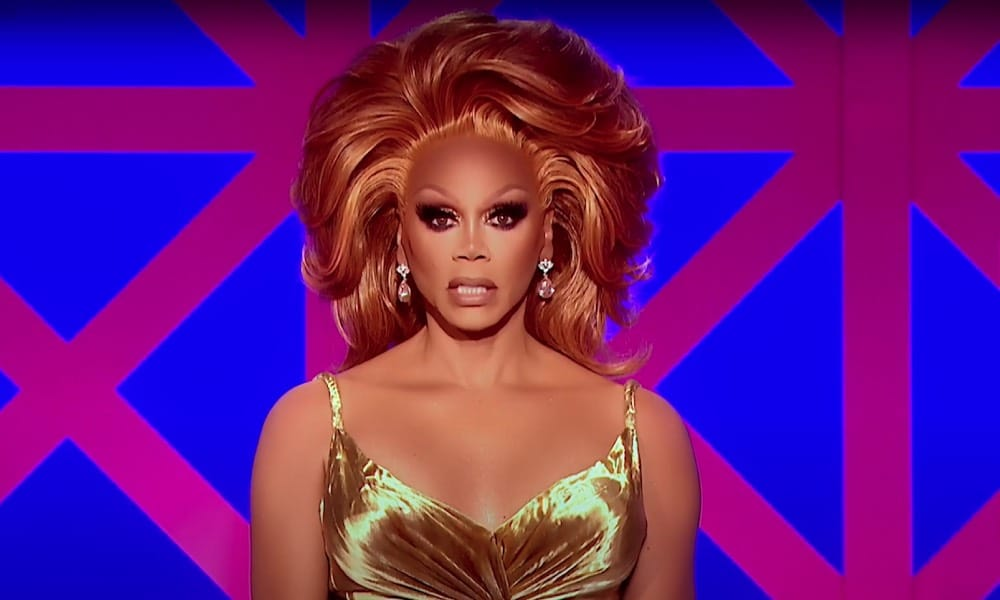 RuPaul in a gold dress with copper hair sitting in front of the Drag Race UK judges' panel backdrop