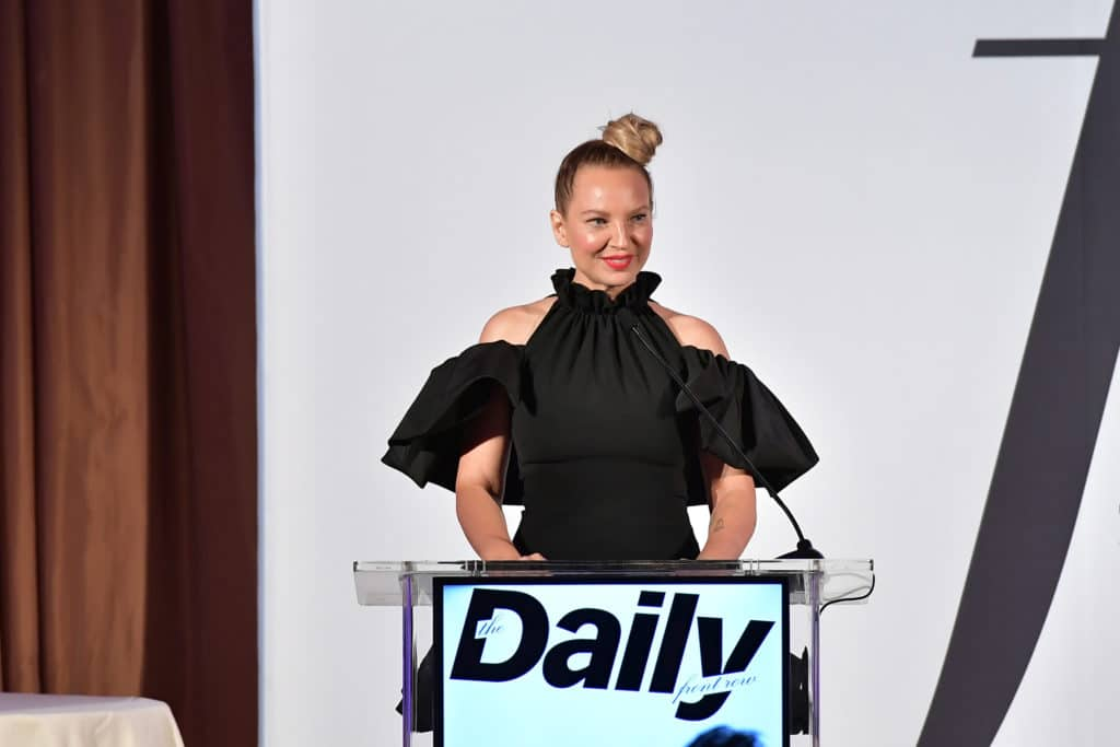 Sia with her hair in a top knot, speaking at a podium