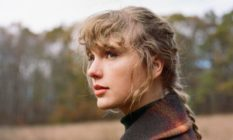 Taylor Swift with her hair in a ponytail, wearing a checked coat, looking off into nature