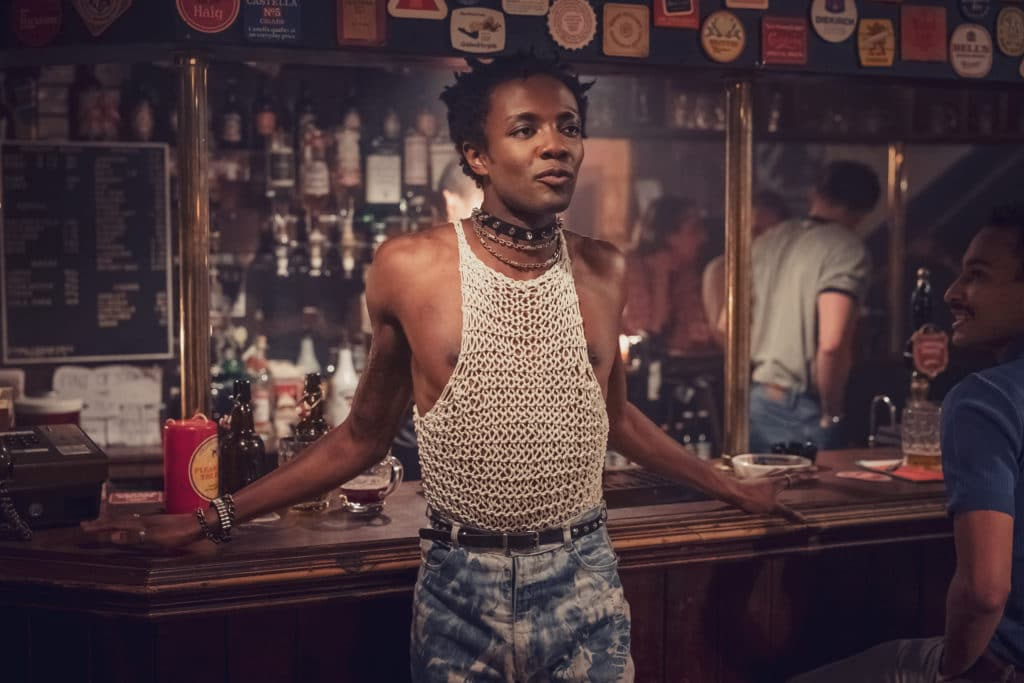 Omari Douglas as Roscoe, leaning against a pub bar, wearing acid-washed jeans and a string vest