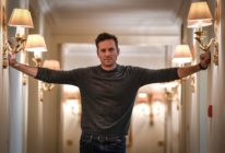 Armie Hammer stretches his arms outwards towards the corridor walls