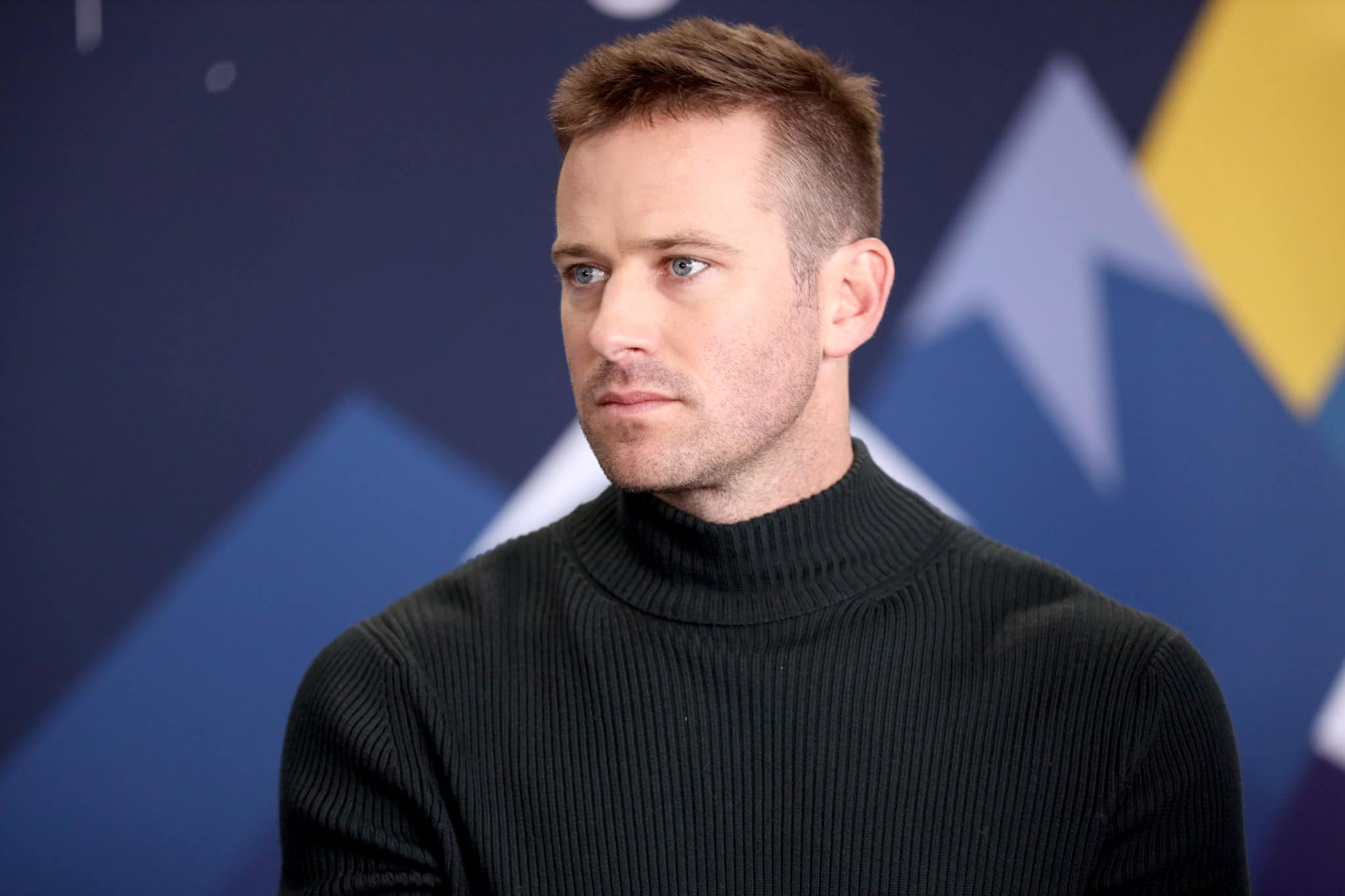 Armie Hammer in a black turtleneck looking to the right