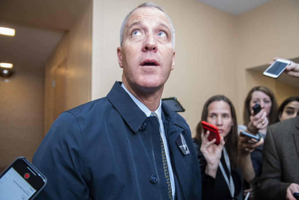 Sean Patrick Maloney looks upwards as he speaks to reporters, their arms raised while holding mobile phones