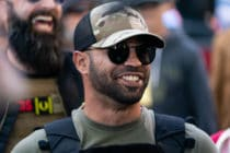 Proud Boy leader Enrique Tarrio smile while wearing a dark green t-shirt and cap