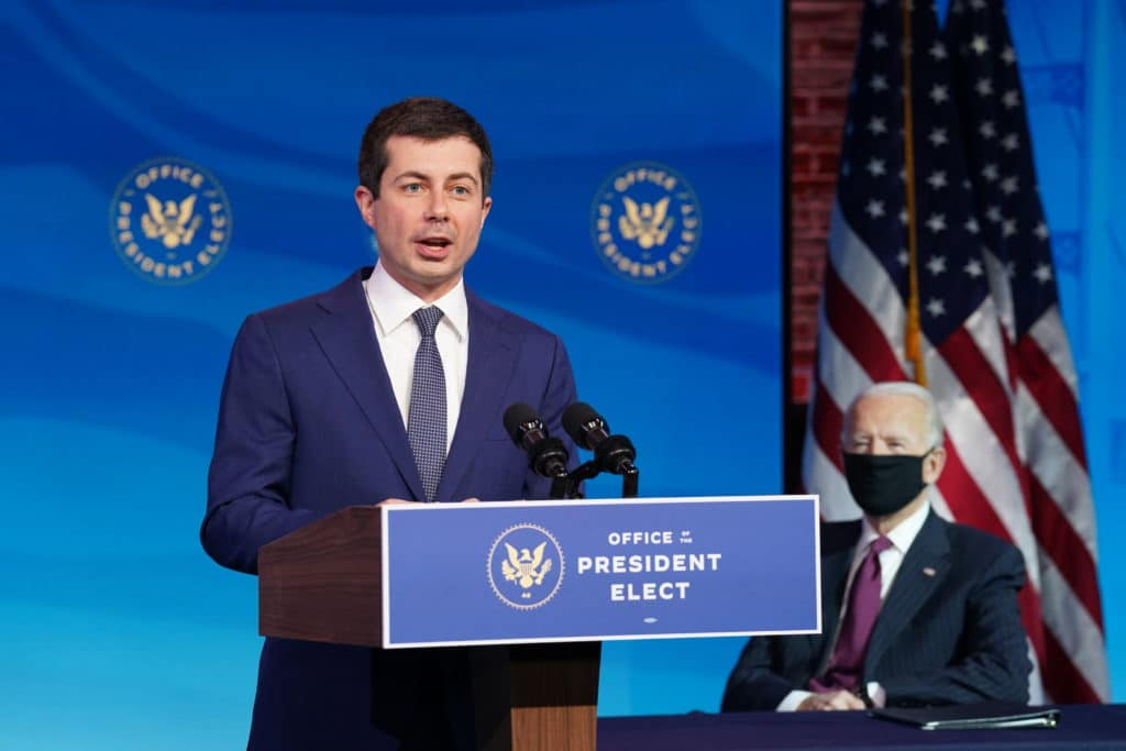 Former Democratic presidential candidate Pete Buttigieg speaks as US President-elect Joe Biden looks on after he was nominated to be Secretary of Transportation
